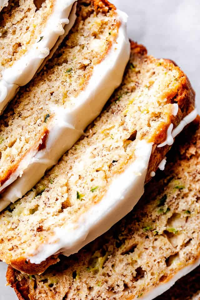 close up shot of zucchini banana bread slices with icing