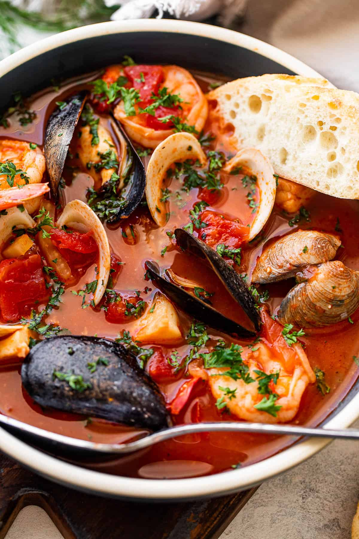 seafood tomato stew in a blue soup bowl served with a slice of crusty bread and a spoon