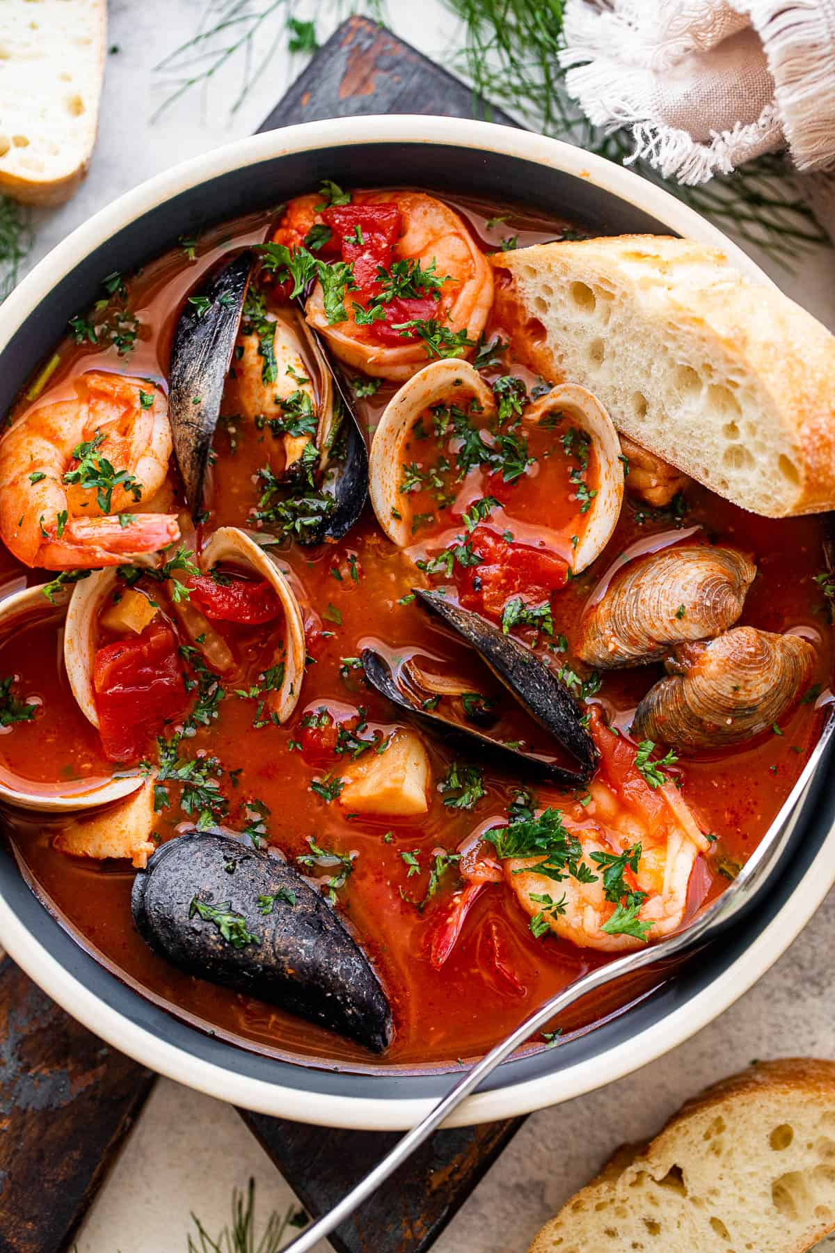 overhead photo of a blue bowl with tomato stew and mussels, clams, cod, and shrimp served with a slice of bread