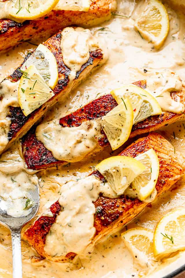 Overhead shot of cooked salmon fillets sitting in a creamy dill sauce