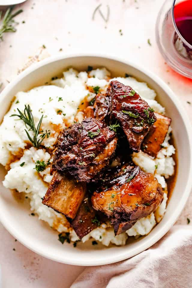 short ribs served over mashed potatoes and a glass of wine to the side
