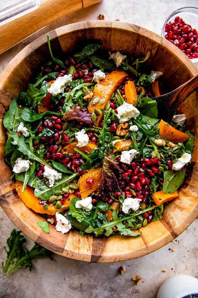 wide overhead shot of wooden salad bowl with salad greens, pomegranates, squash, and goat cheese