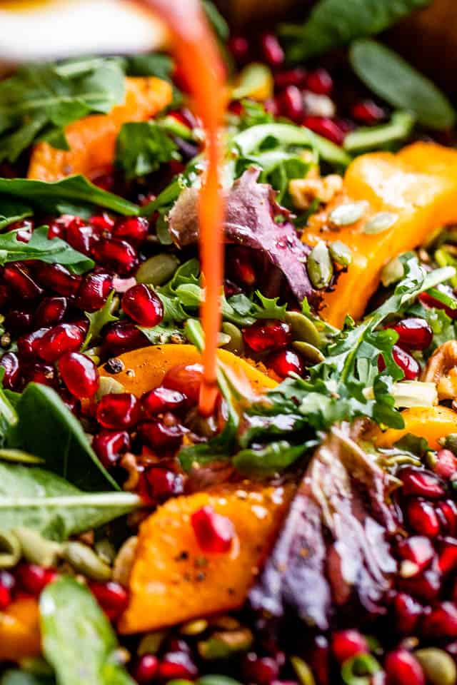 pouring pomegranate salad dressing over butternut squash salad