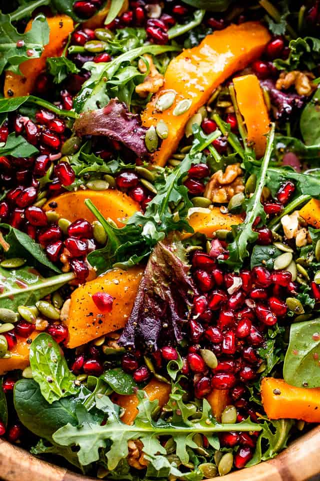 overhead shot of salad greens topped with squash, pomegranate arils, and nuts