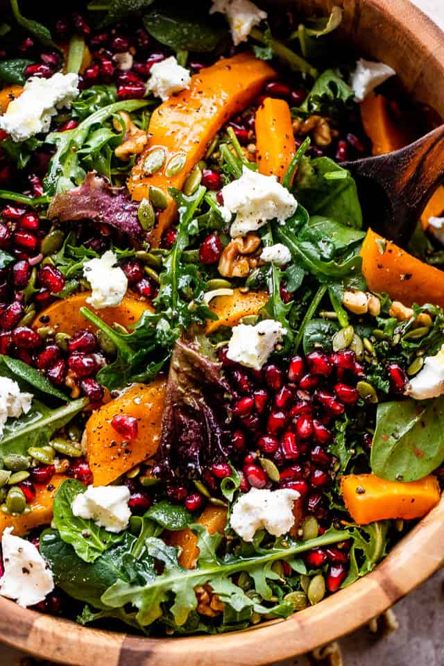 overhead shot of salad greens in a wooden salad bowl, and topped with squash, pomegranate arils, nuts, and goat cheese