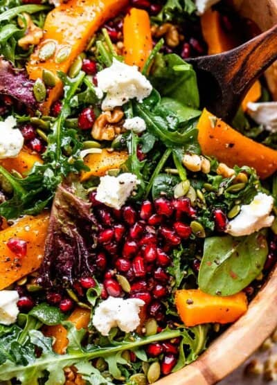 close up shot of salad greens topped with squash, pomegranate arils, nuts, and goat cheese