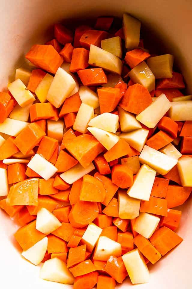 raw chunks of sweet potatoes and white potatoes in the insert of a slow ooker
