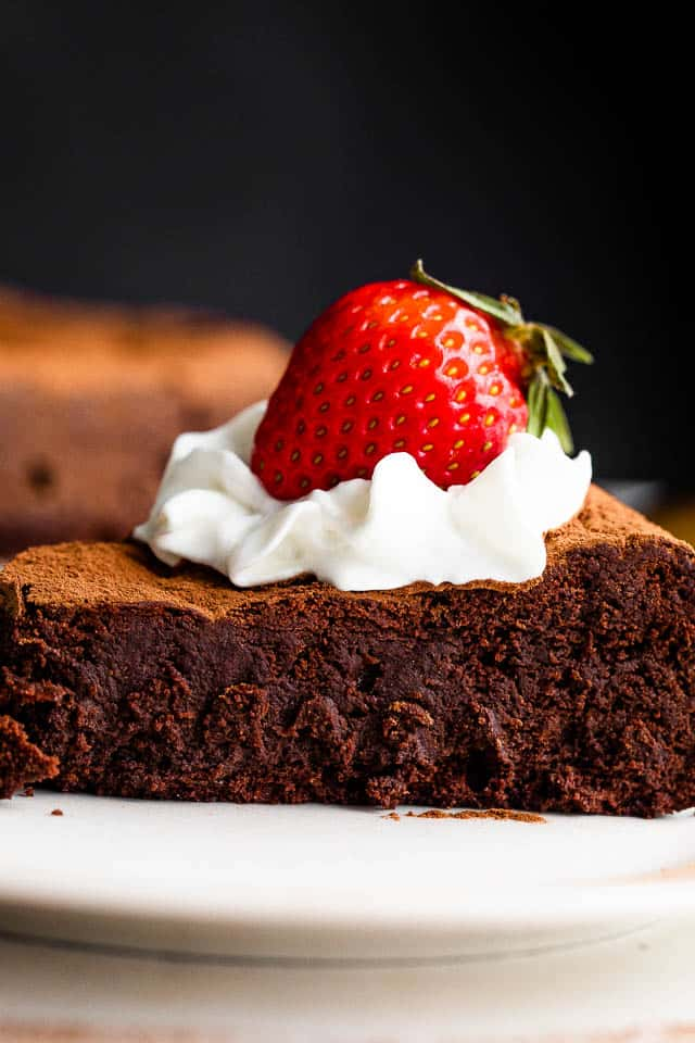 side shot of a chocolate cake slice topped with whipped cream and strawberry