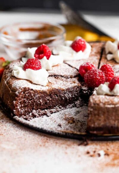 side shot of flourless chocolate cake cut into slices and topped with powdered sugar, whipped cream, and raspberries