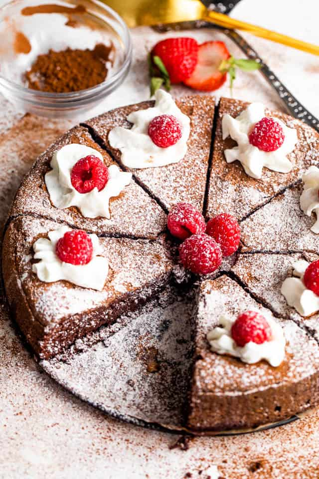 wide shot of a sliced flourless chocolate cake topped with powdered sugar, berries, and cream