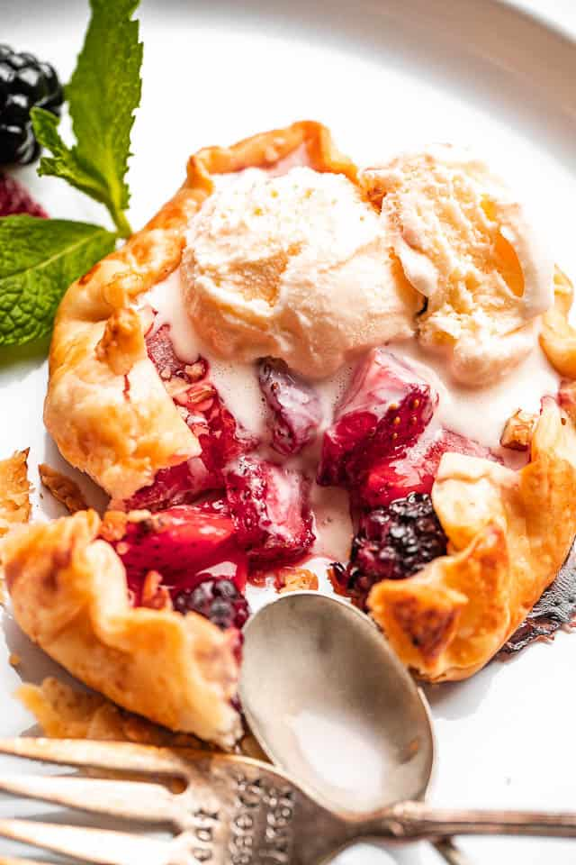Mini Berry Galettes topped with vanilla ice cream scoop.