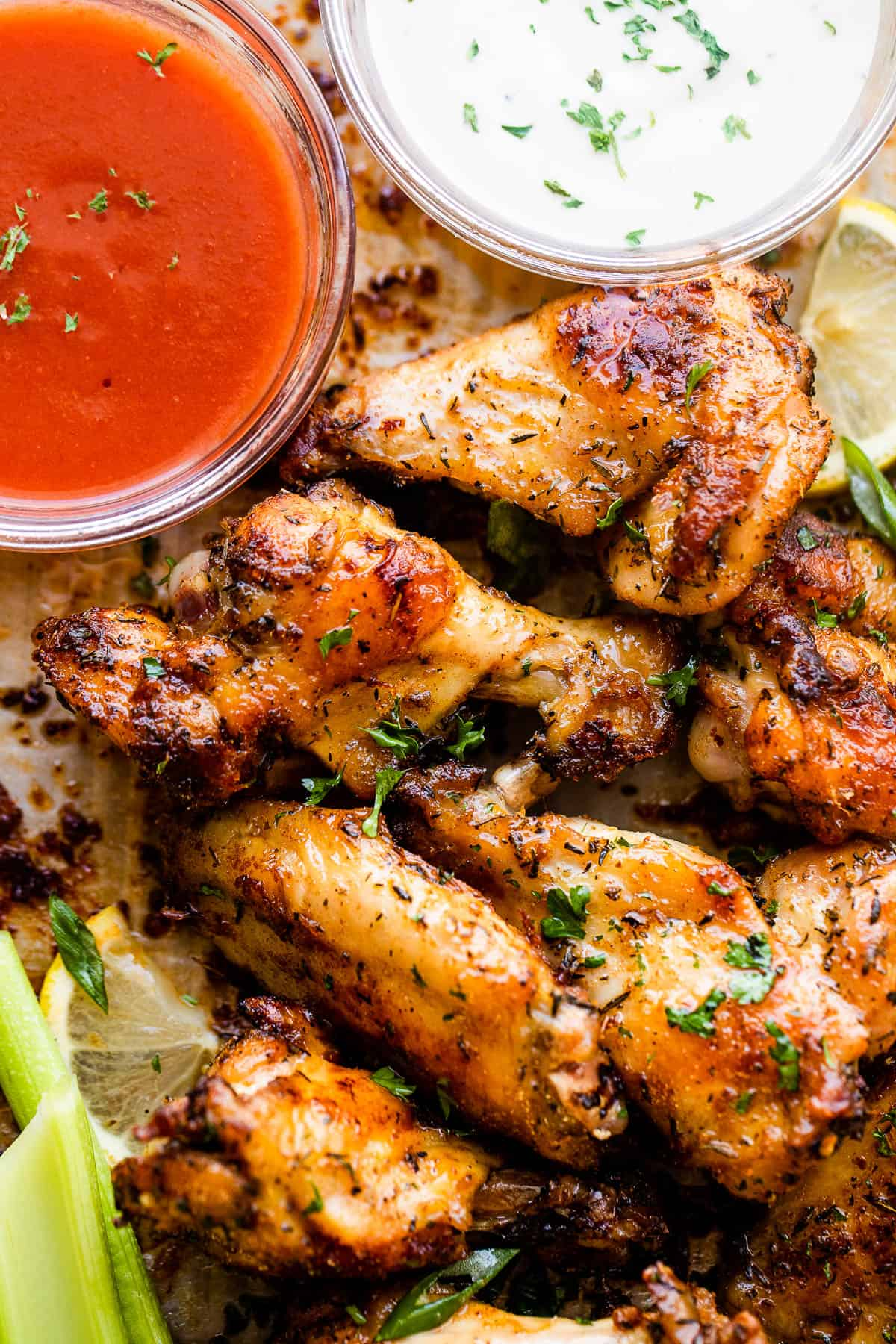 chicken wings on a platter served with sriracha sauce, ranch, and celery sticks.