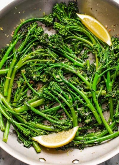 closeup shot of sauteed broccolini served with lemon wedges