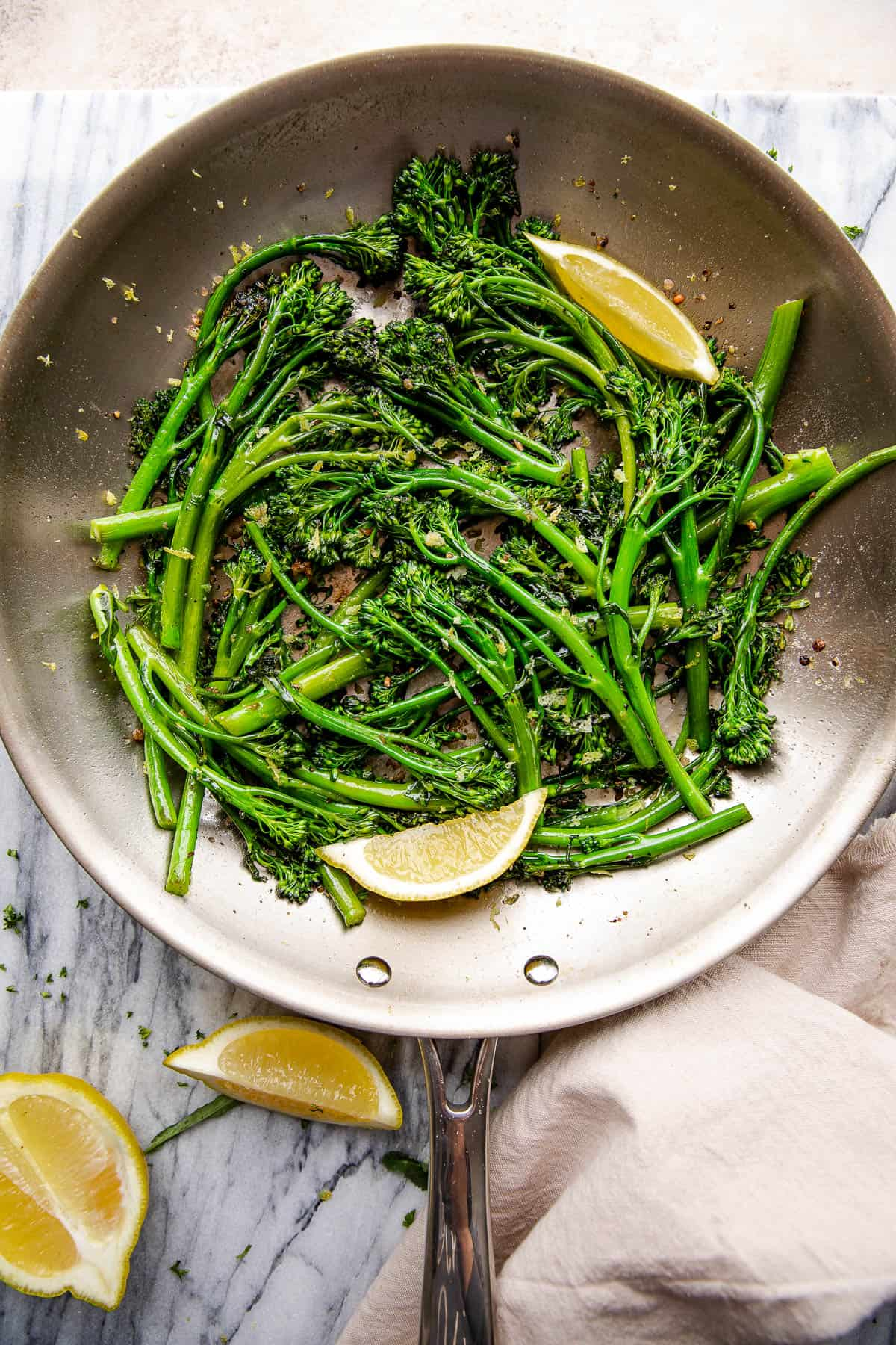 overhead shot of sauteed broccolini and lemon wedges pictured in a stainless steel skillet