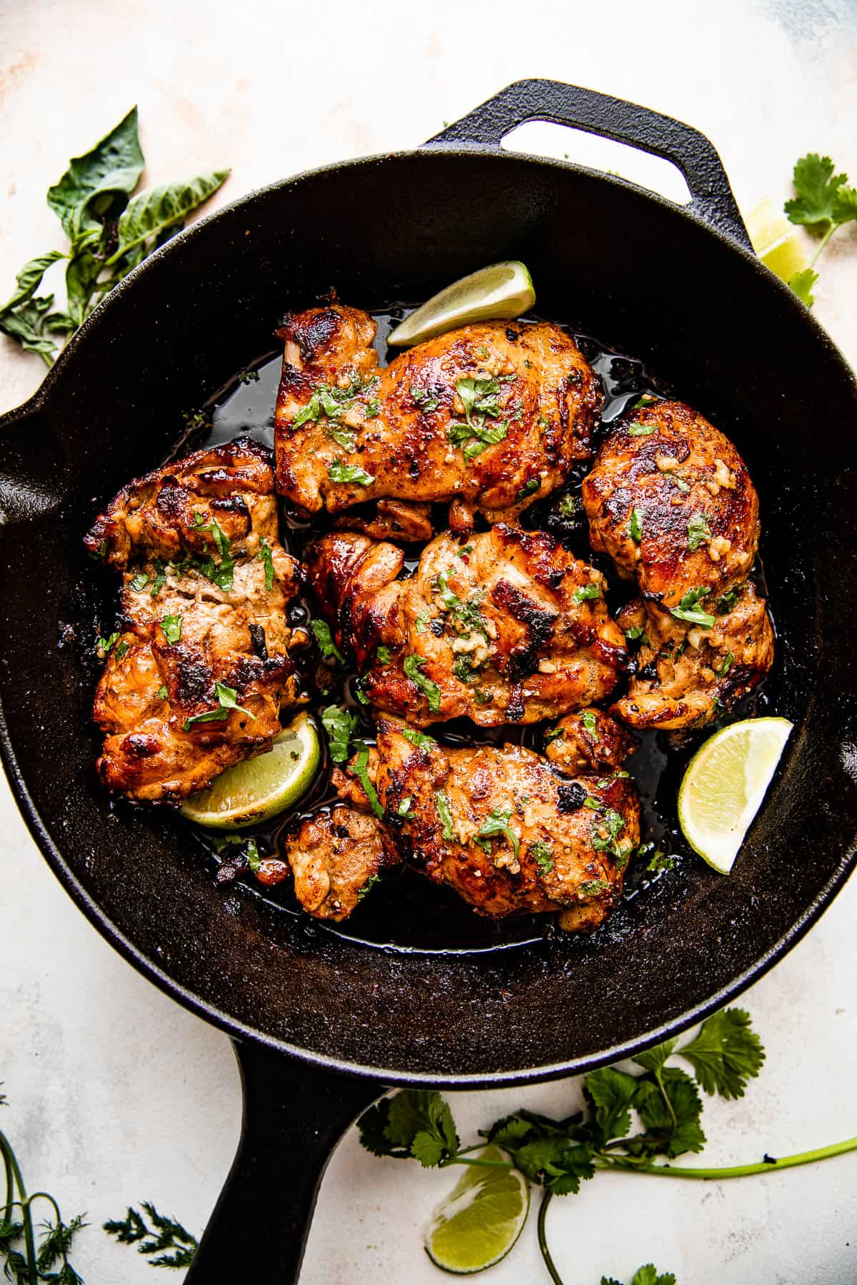 overhead picture of chicken thighs cooking in a cast iron skillet