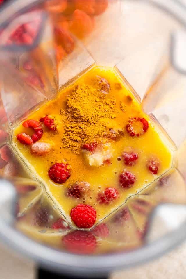 orange juice, raspberries, and turmeric powder in a blender