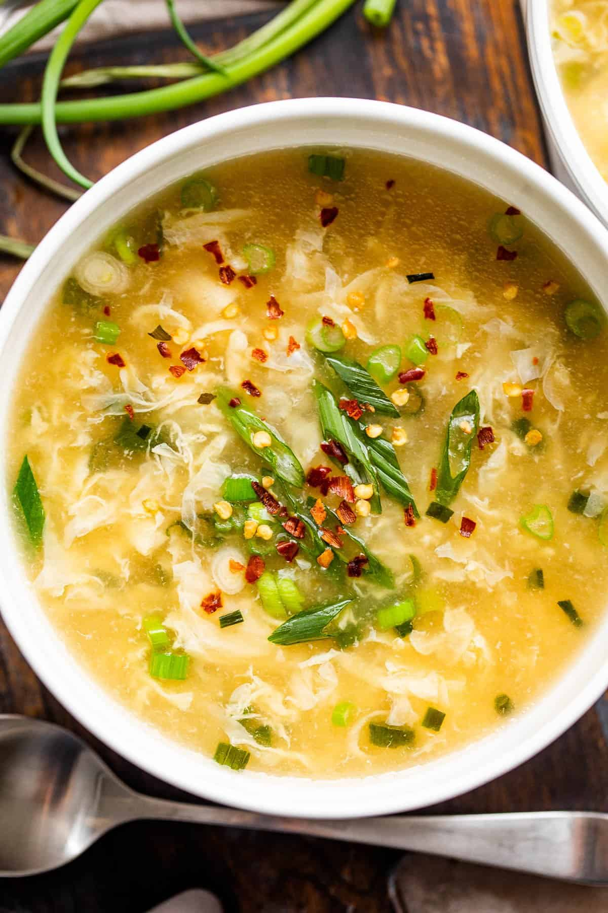 overhead shot of egg drop soup in a white soup bowl