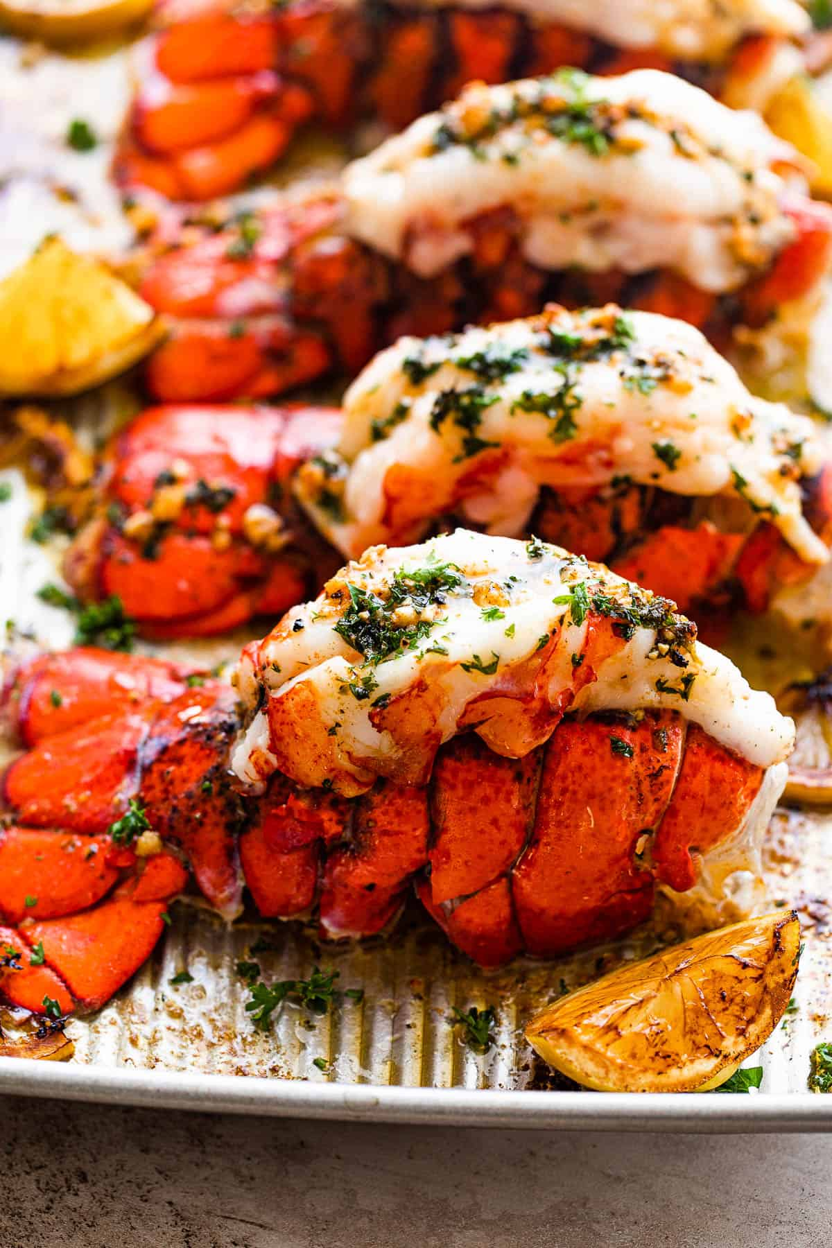 A Close-up Shot of a Baked Lobster Tail Next to a Lemon Wedge