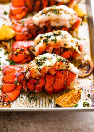 Four Cooked Lobster Tails Lined Up on a Baking Sheet