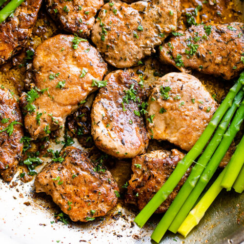 stainless skillet with pork medallions and asparagus