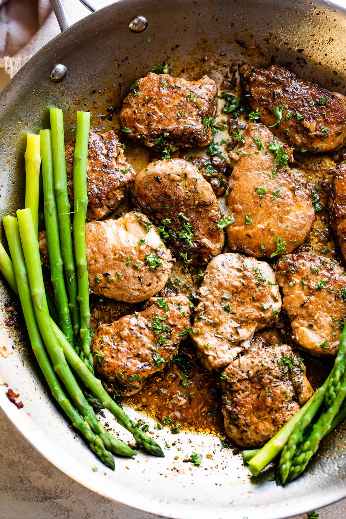 pork medallions in a skillet with stalks of asparagus to the side