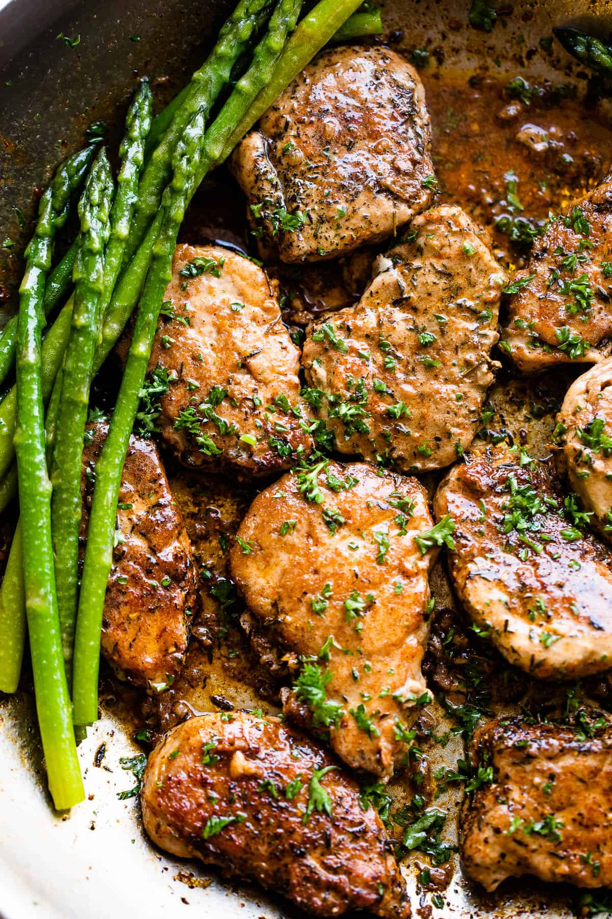 close up picture of pork medallions in a skillet with stalks of asparagus to the side