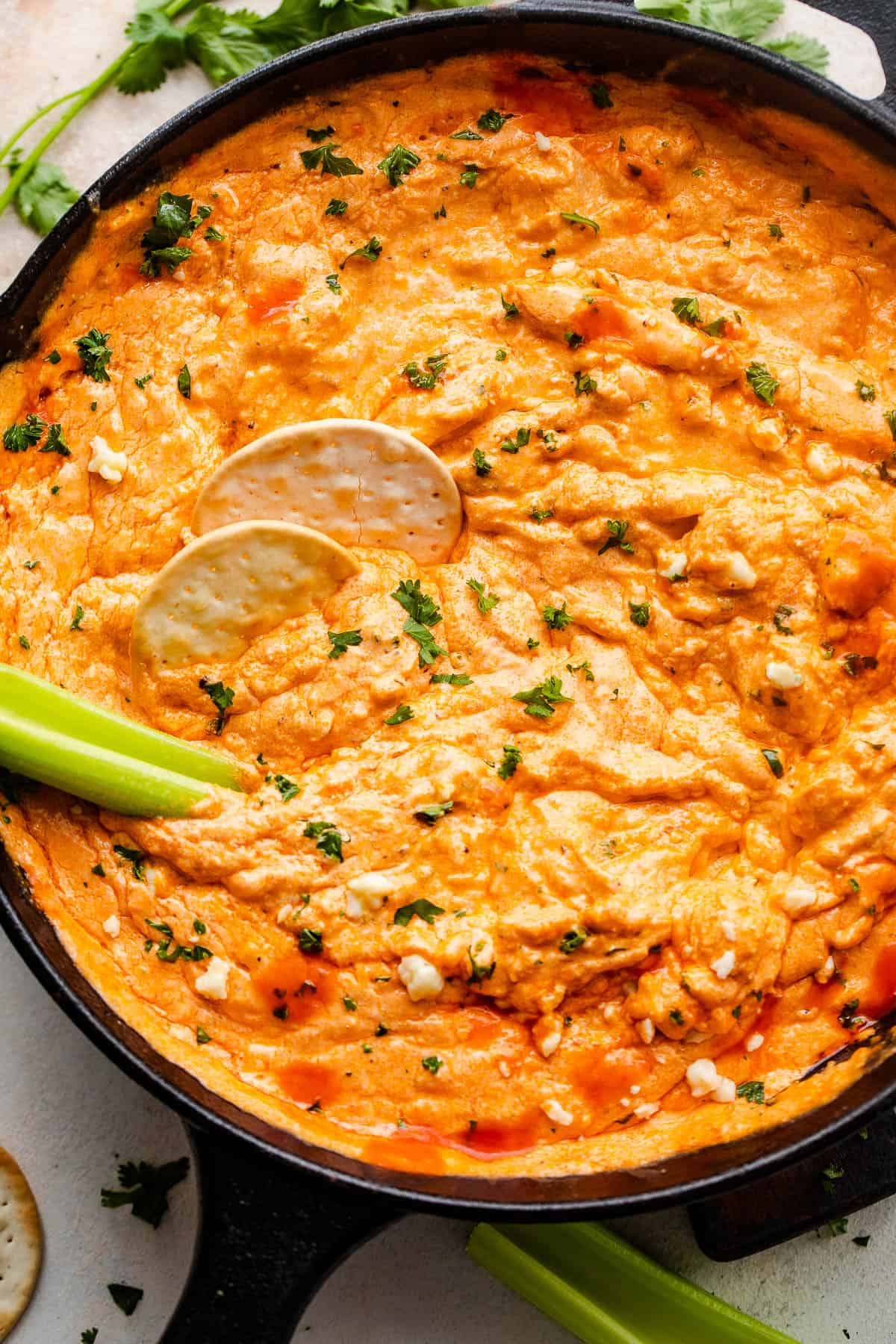 overhead shot of buffalo chicken dip in a cast iron skillet with two crackers and celery sticks in the dip