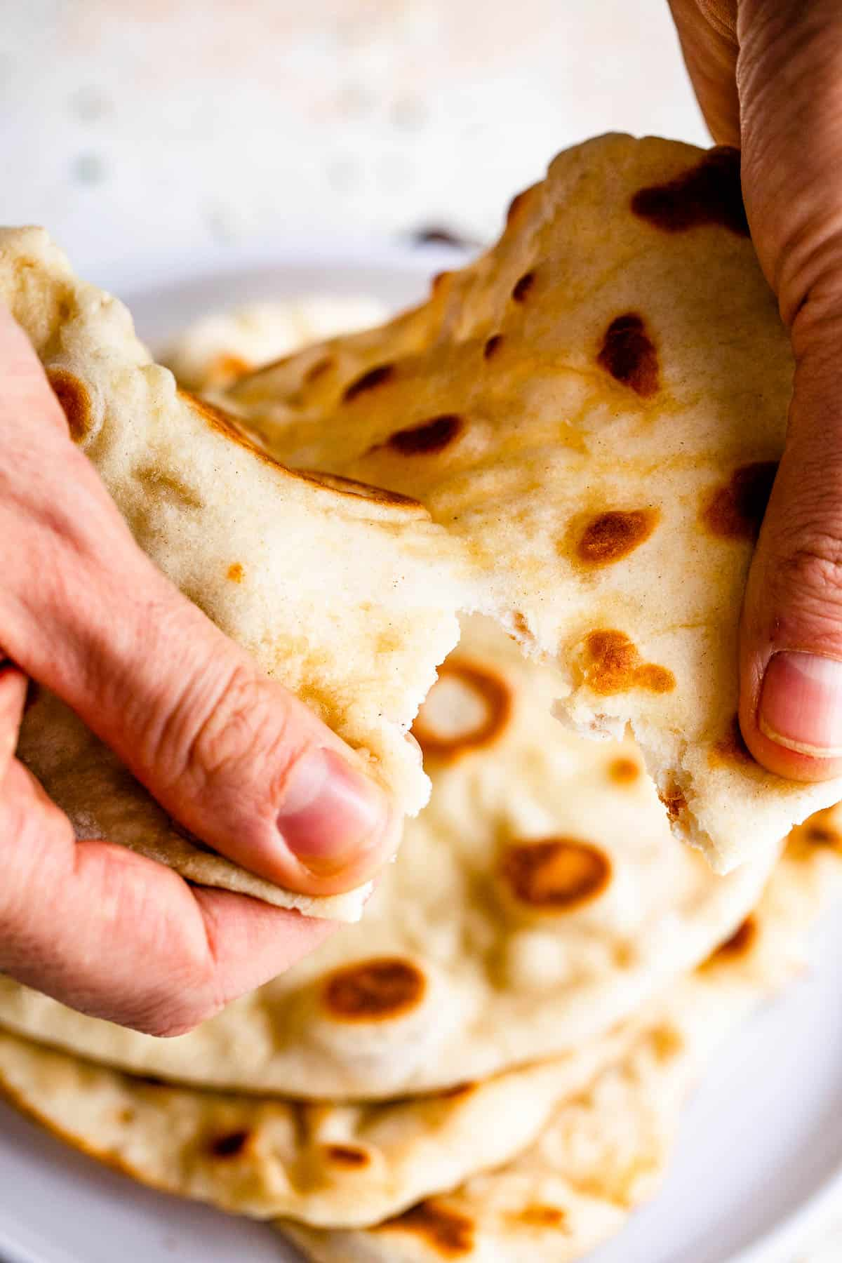 tearing naan bread with hands