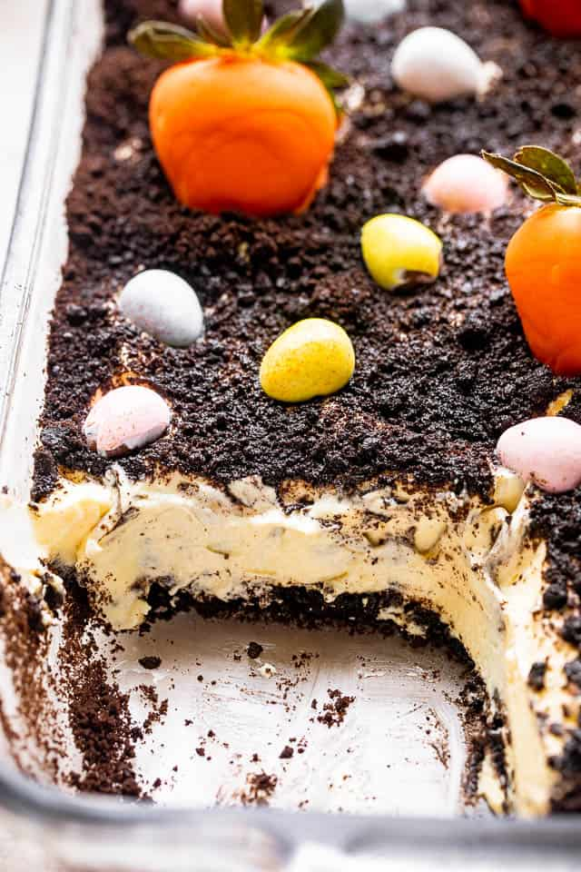 oreo dirt cake in a glass baking dish topped with egg candies and orange strawberries