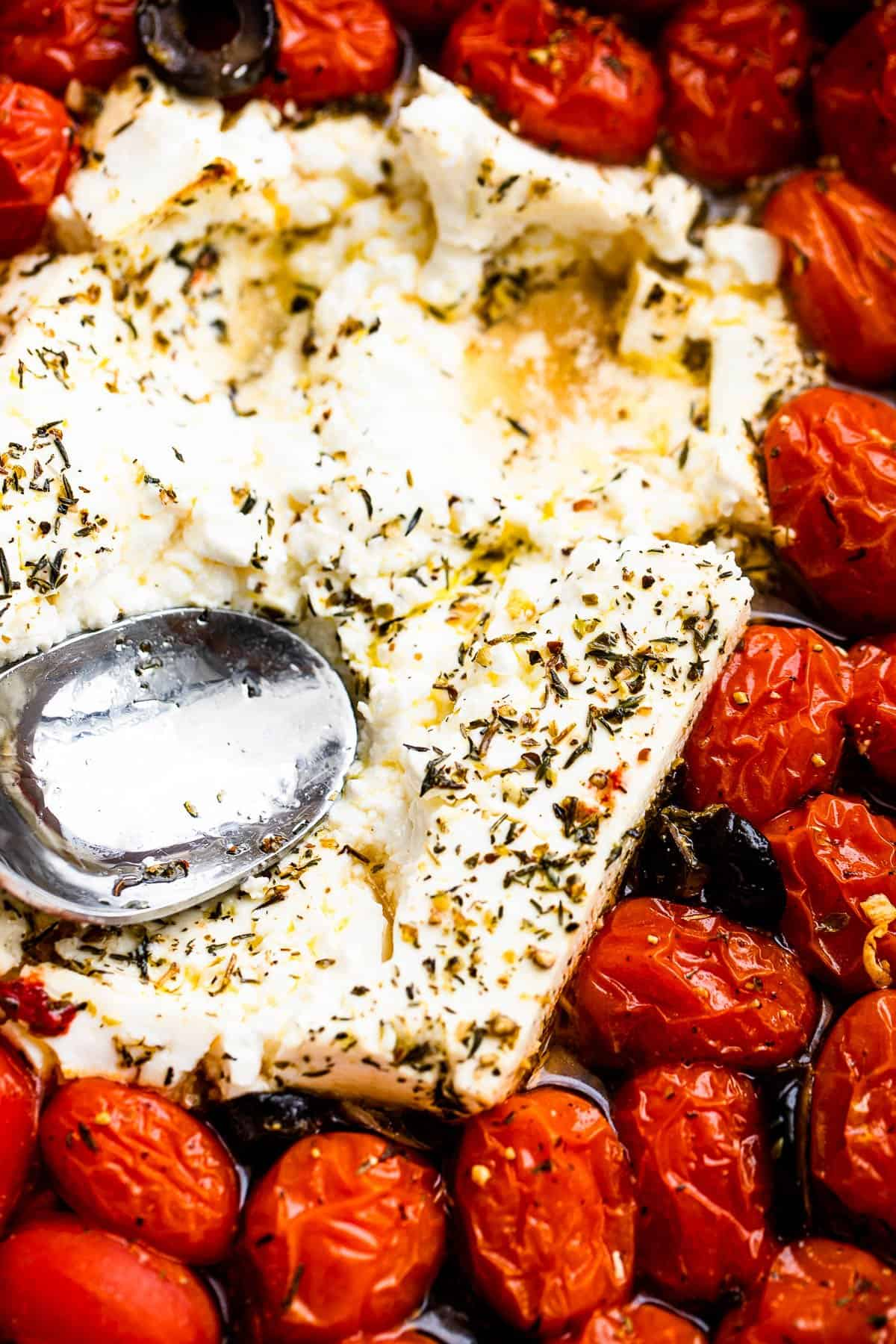 pressing baked feta with the back of a spoon
