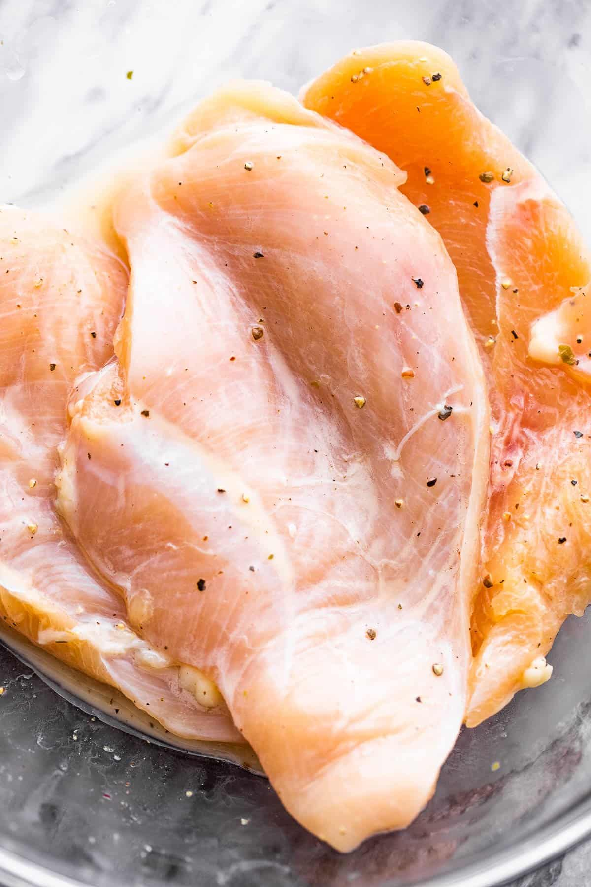 raw chicken breasts in a glass bowl