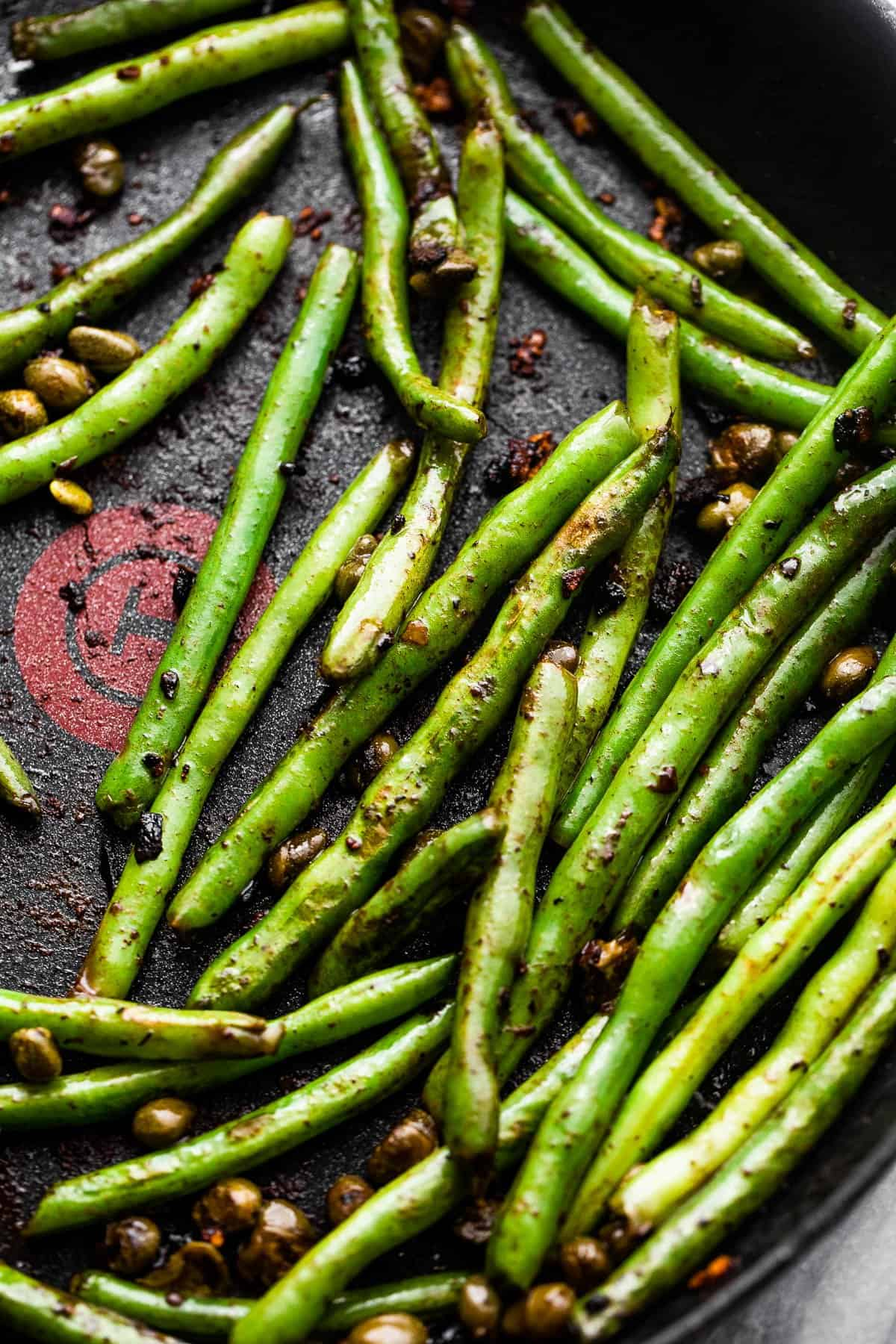 cooking green beans in a black skillet