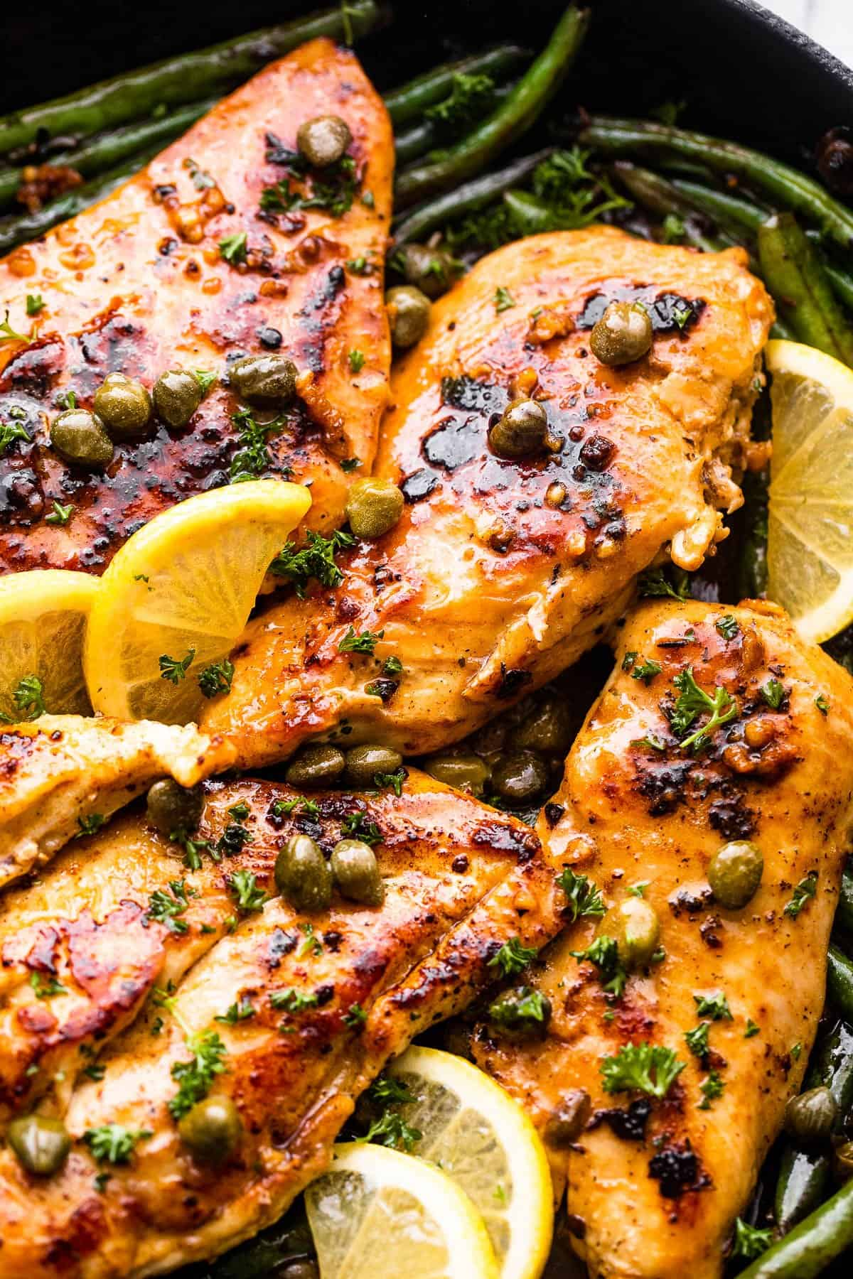 up close photo of chicken breasts topped with capers and lemon slices