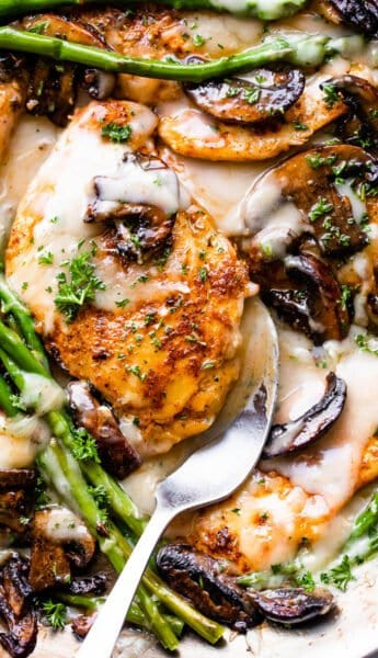 chicken cutlets in creamy madeira sauce with asparagus stalks and sliced mushrooms