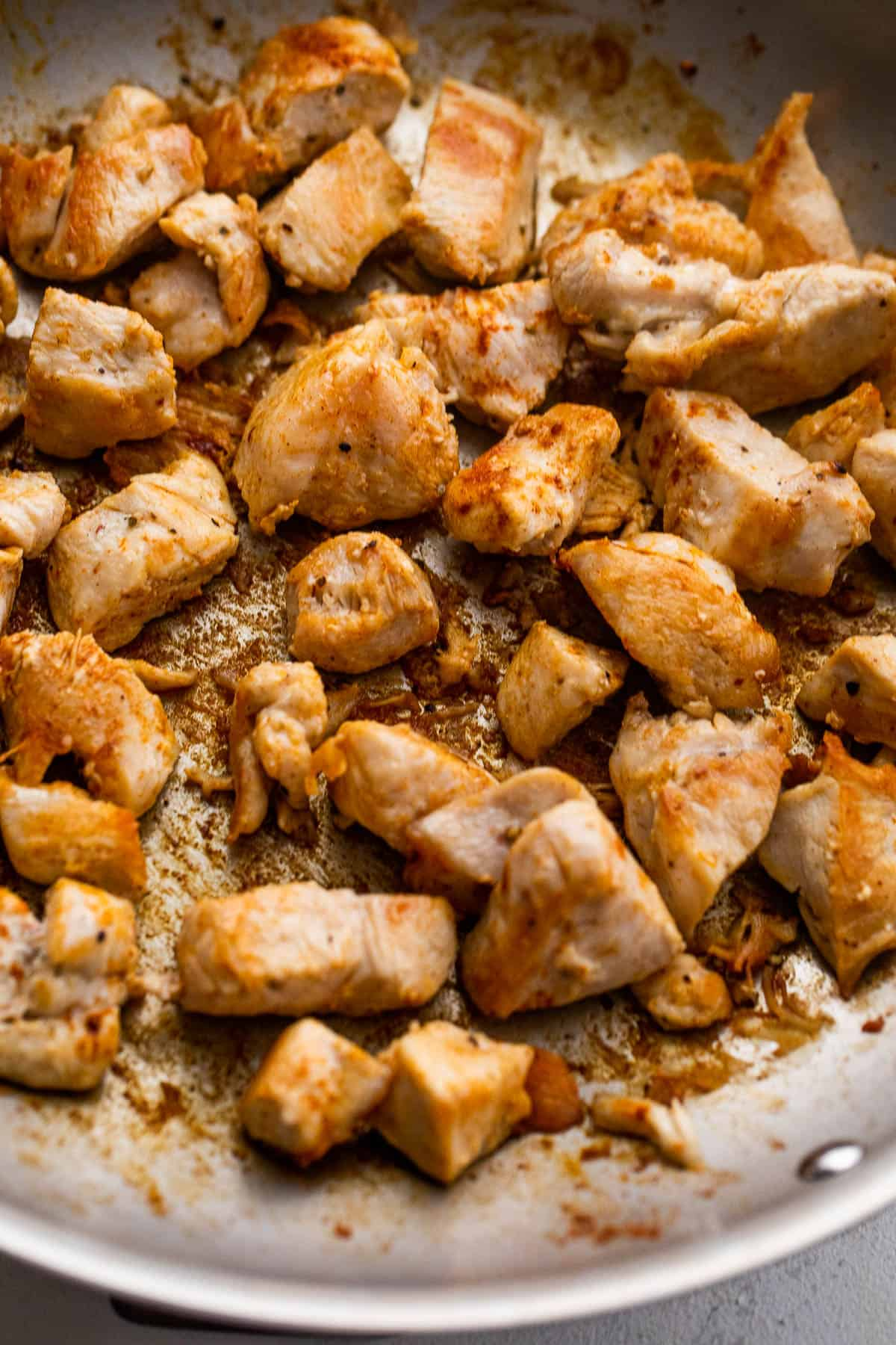 cooking chunks of chicken in a skillet
