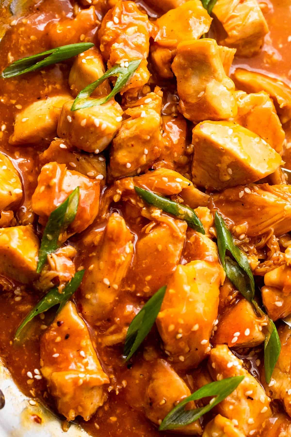 up close shot of chicken bites in orange sauce and topped with sesame seeds and green onions