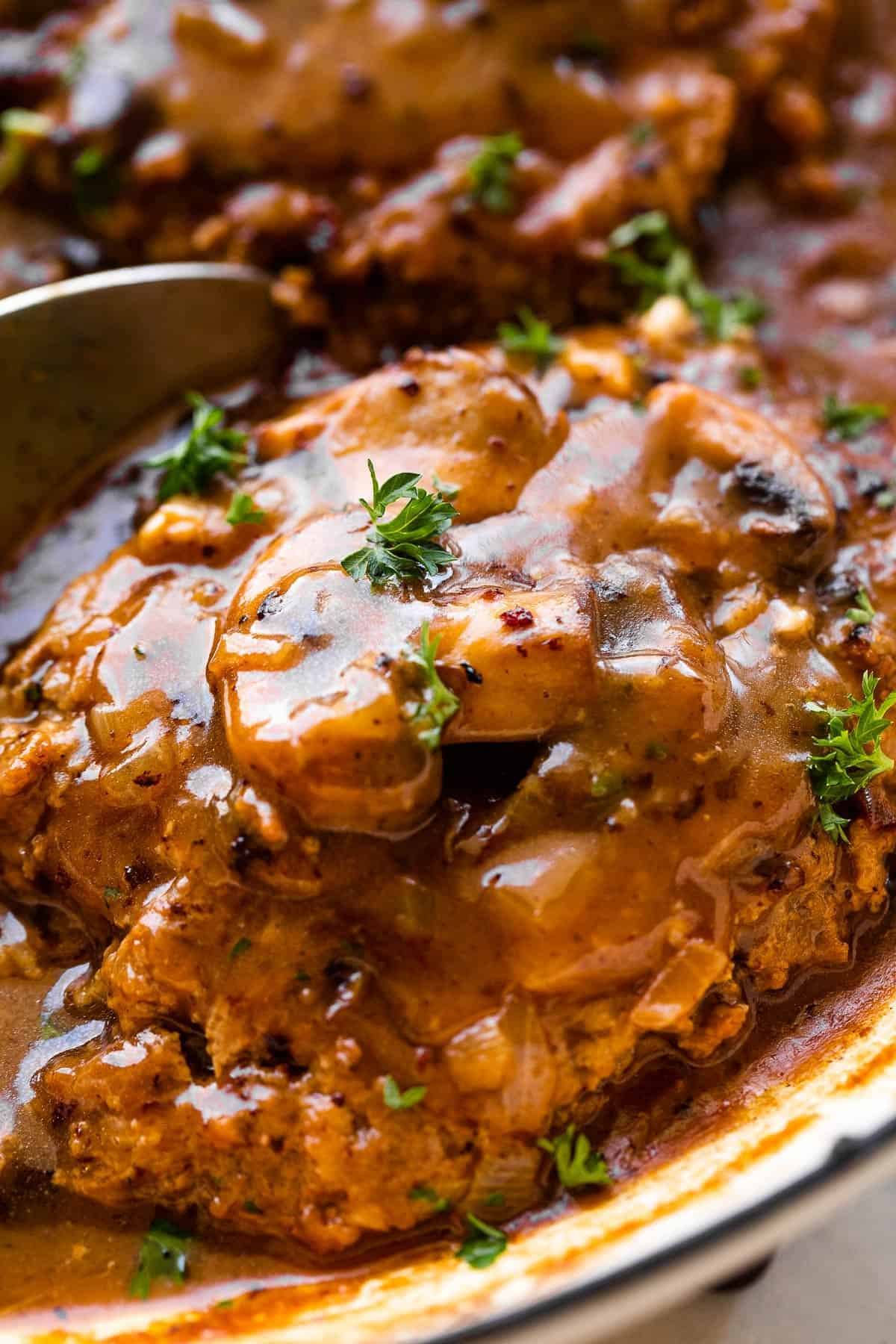up close shot of salisbury steak topped with mushrooms and gravy