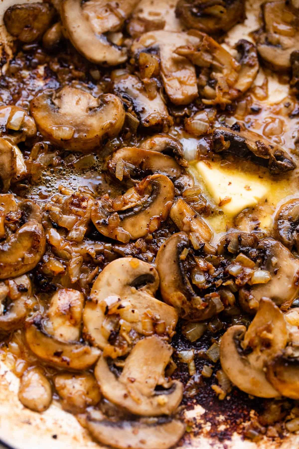 cooking sliced mushrooms in a white skillet