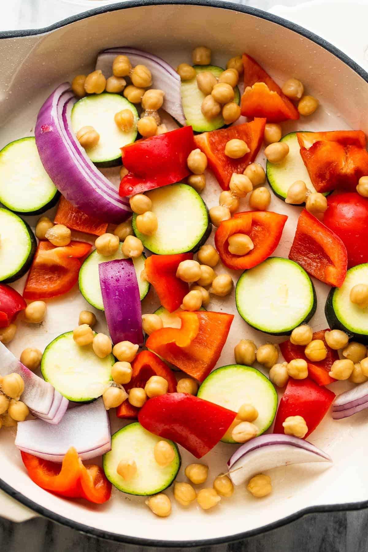 arranged zucchini slices, chickpeas, red bell pepper, and red onions in a white skillet