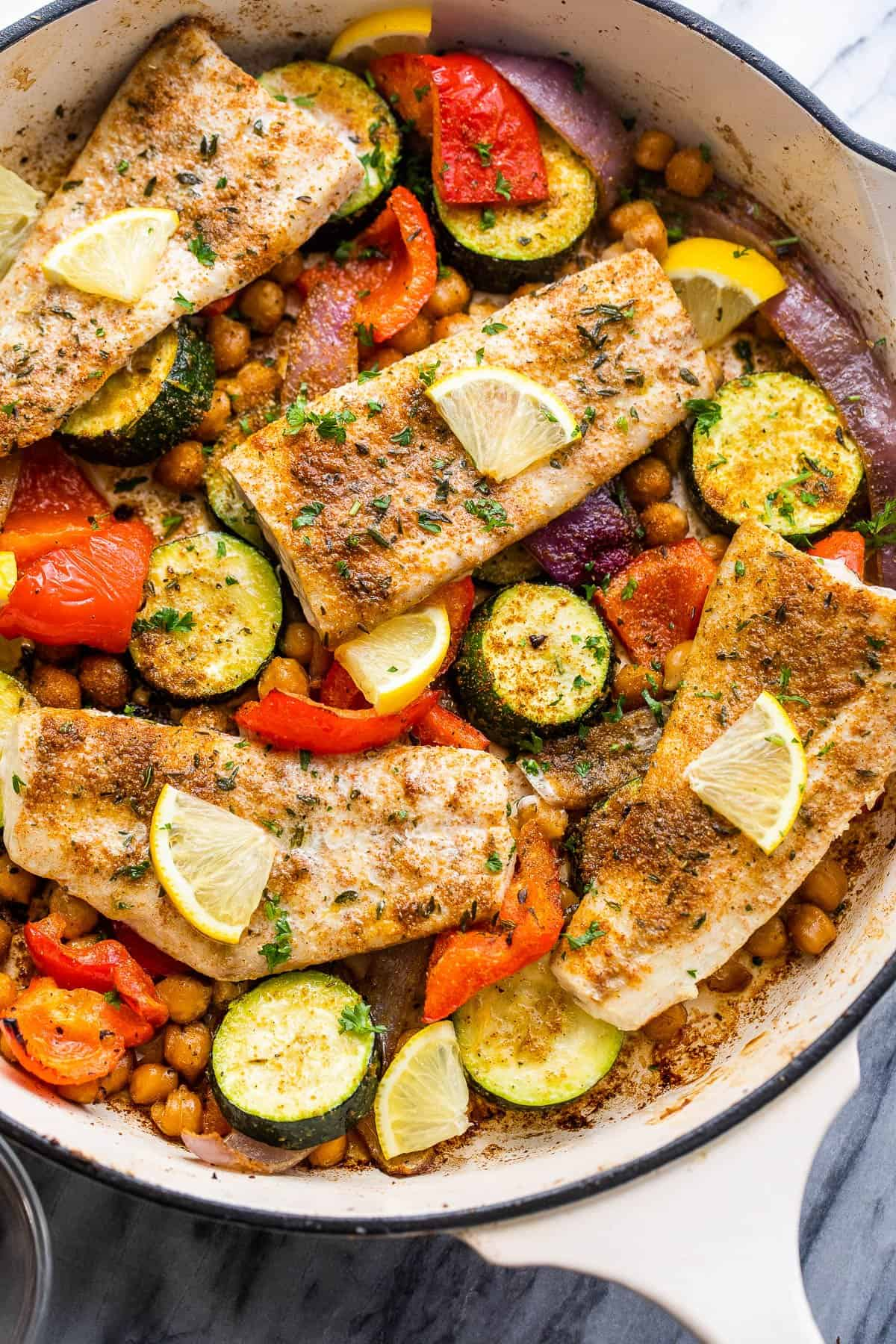 four mahi mahi fillets arranged over zucchini, chickpeas, onions, and peppers