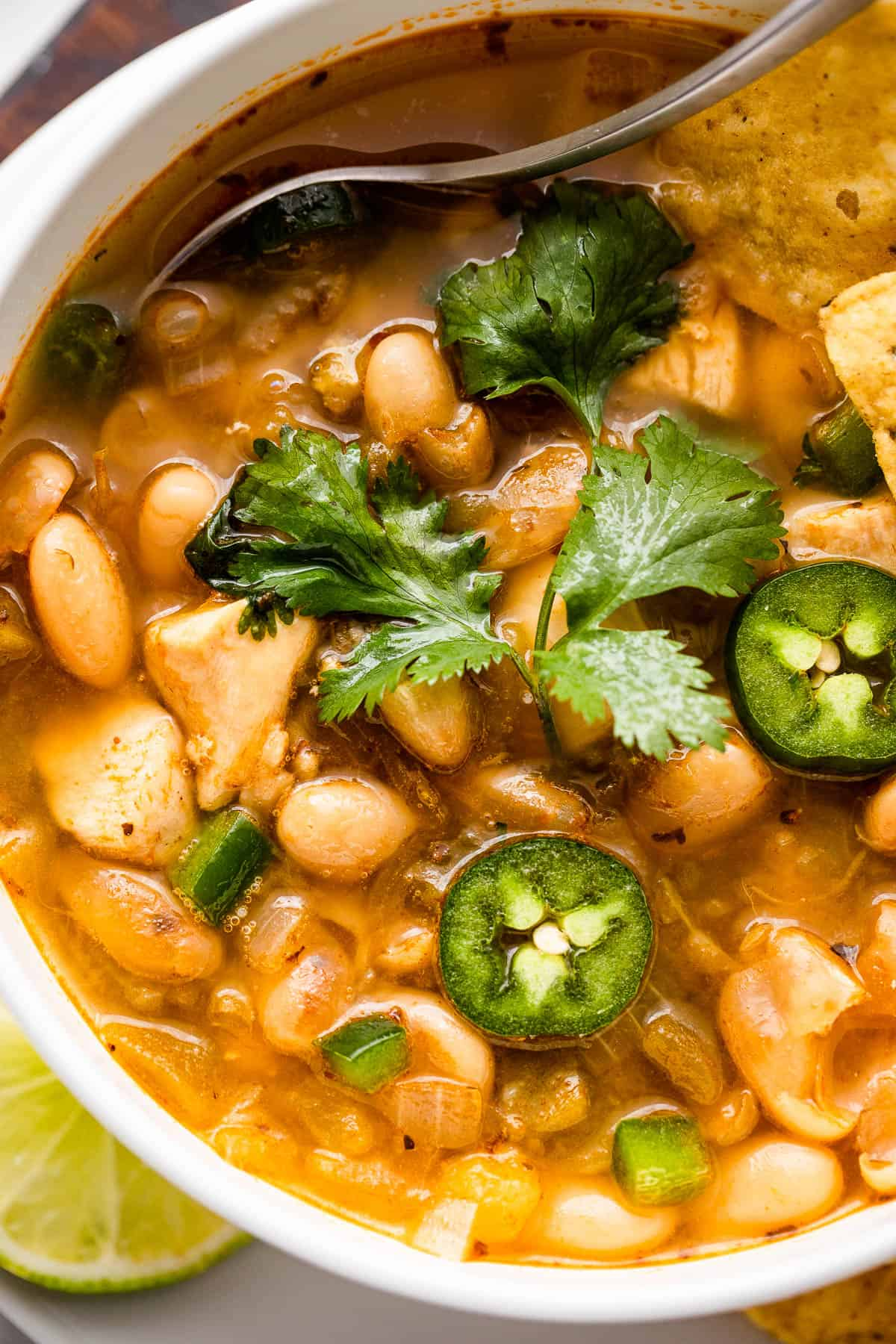 overhead shot of chicken chili with beans in a soup bowl topped with jalapeno slices and cilantro leaves
