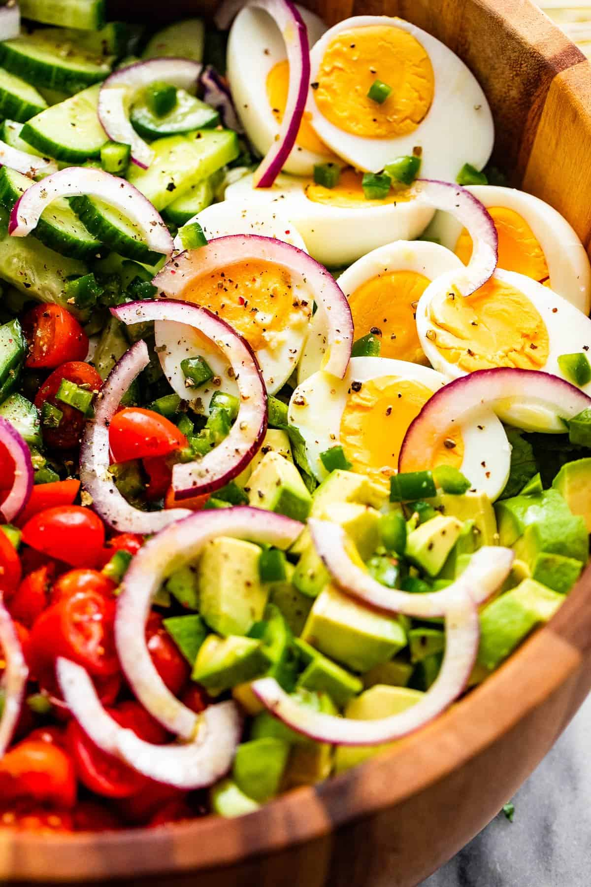 close up of sliced red onions, halved hard boiled eggs, chopped avocado, sliced cherry tomatoes, and sliced cucumbers