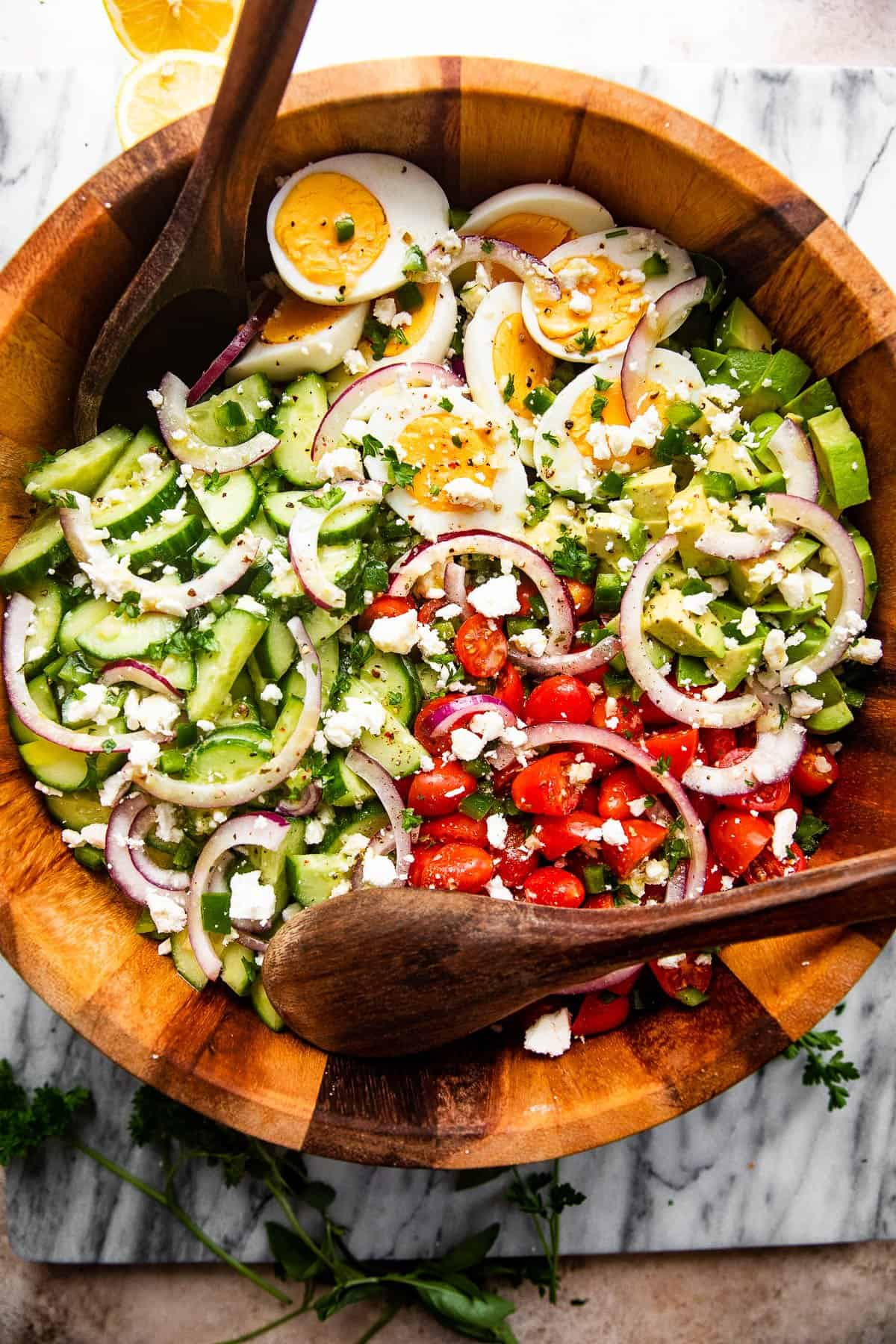 overhead shot of a wooden salad bowl filled with sliced red onions, halved hard boiled eggs, chopped avocado, sliced cherry tomatoes, and sliced cucumbers and topped with feta cheese