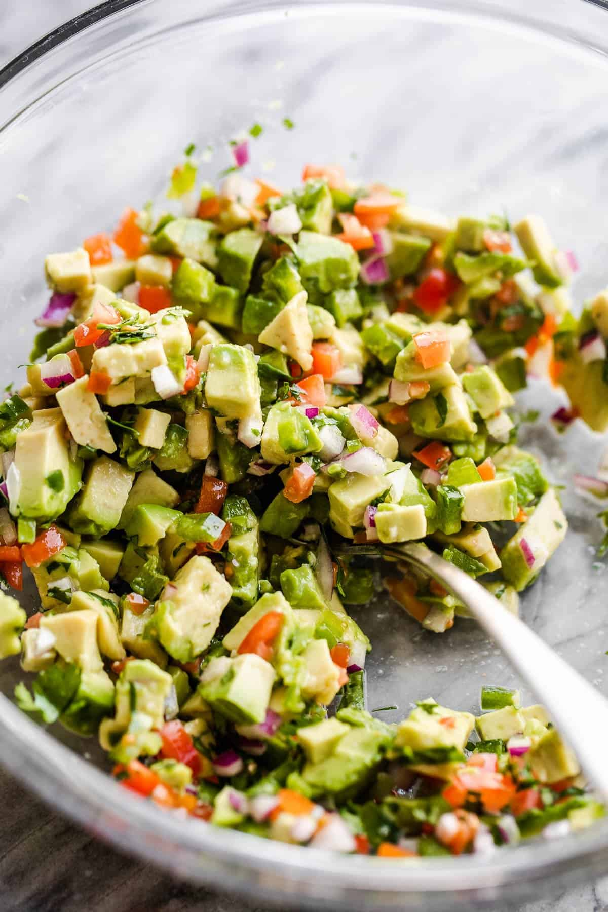 preparing avocado salsa in a glass bowl