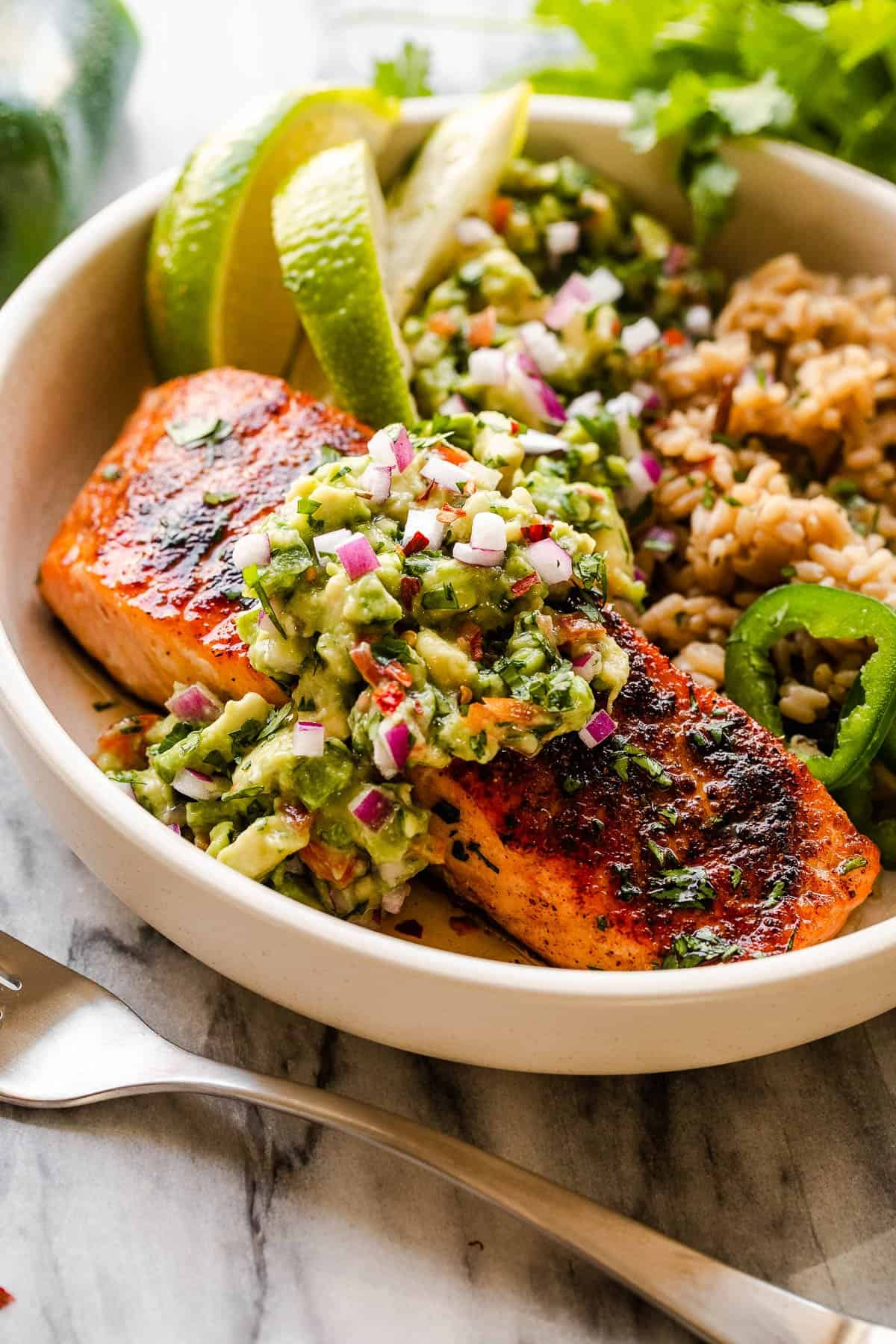 salmon fillet in a bowl atop of rice and served with avocado salsa