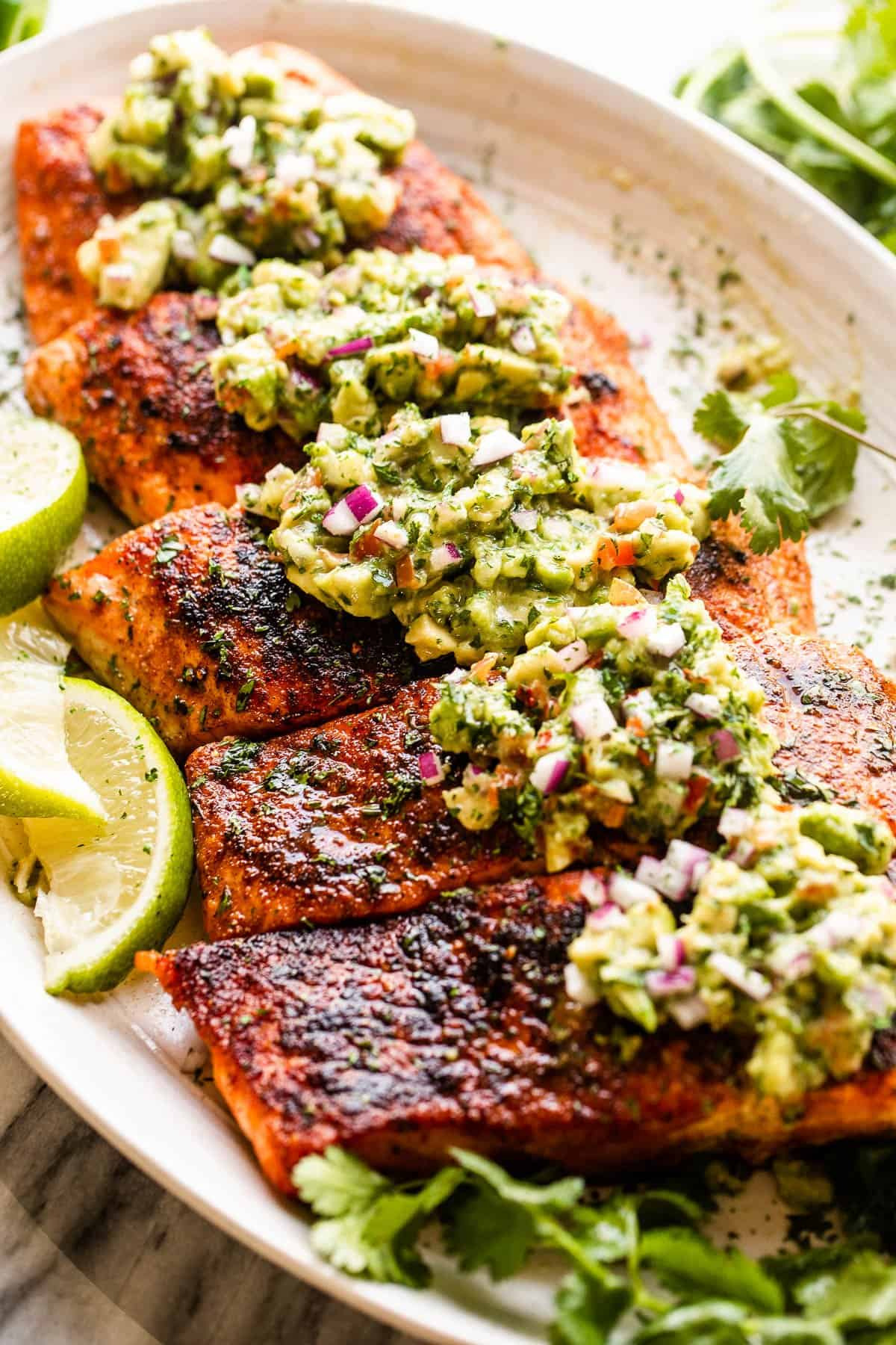 side shot of grilled salmon fillets topped with avocado salsa