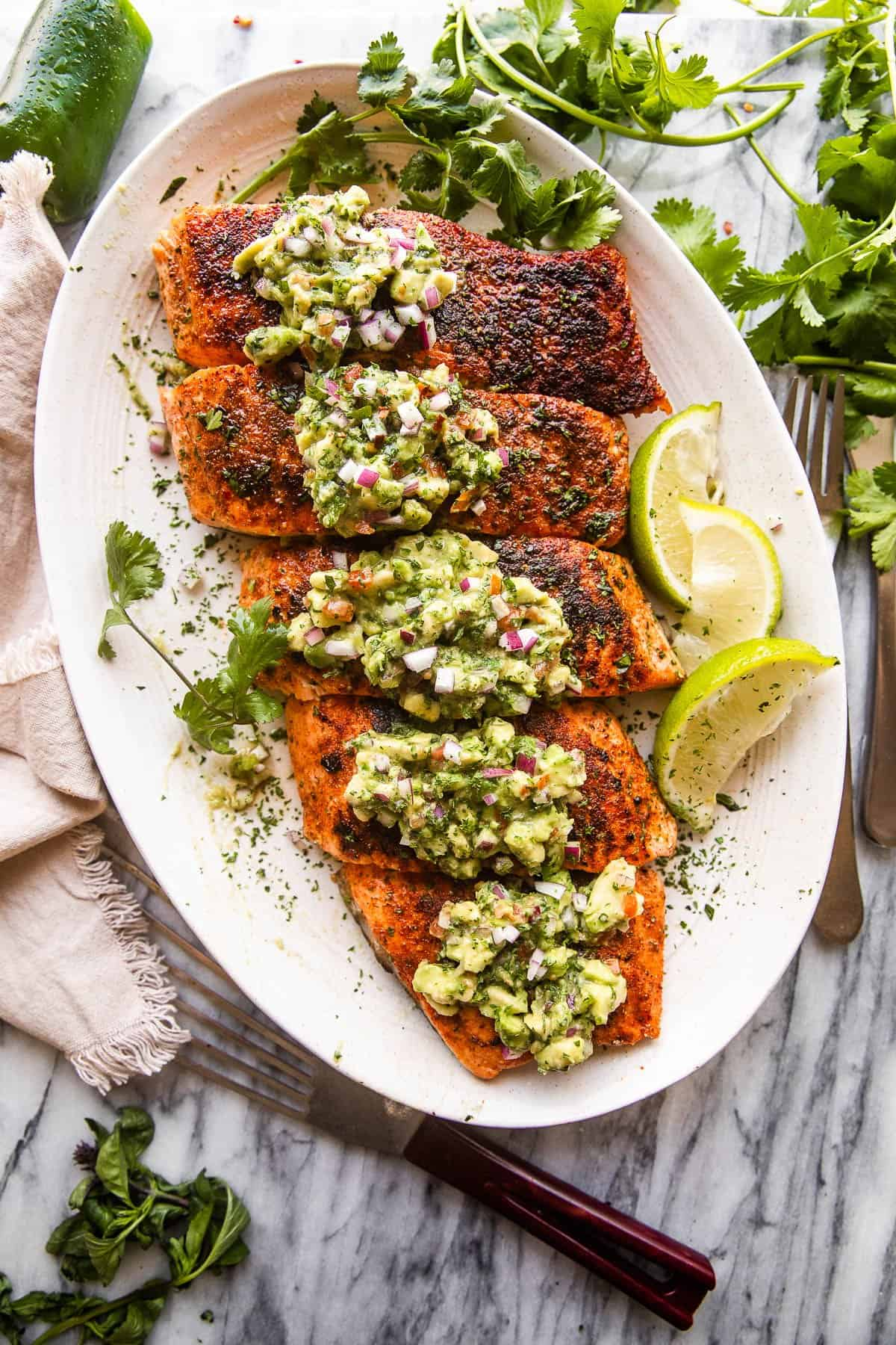 overhead shot of a large plate with grilled salmon fillets topped with avocado salsa