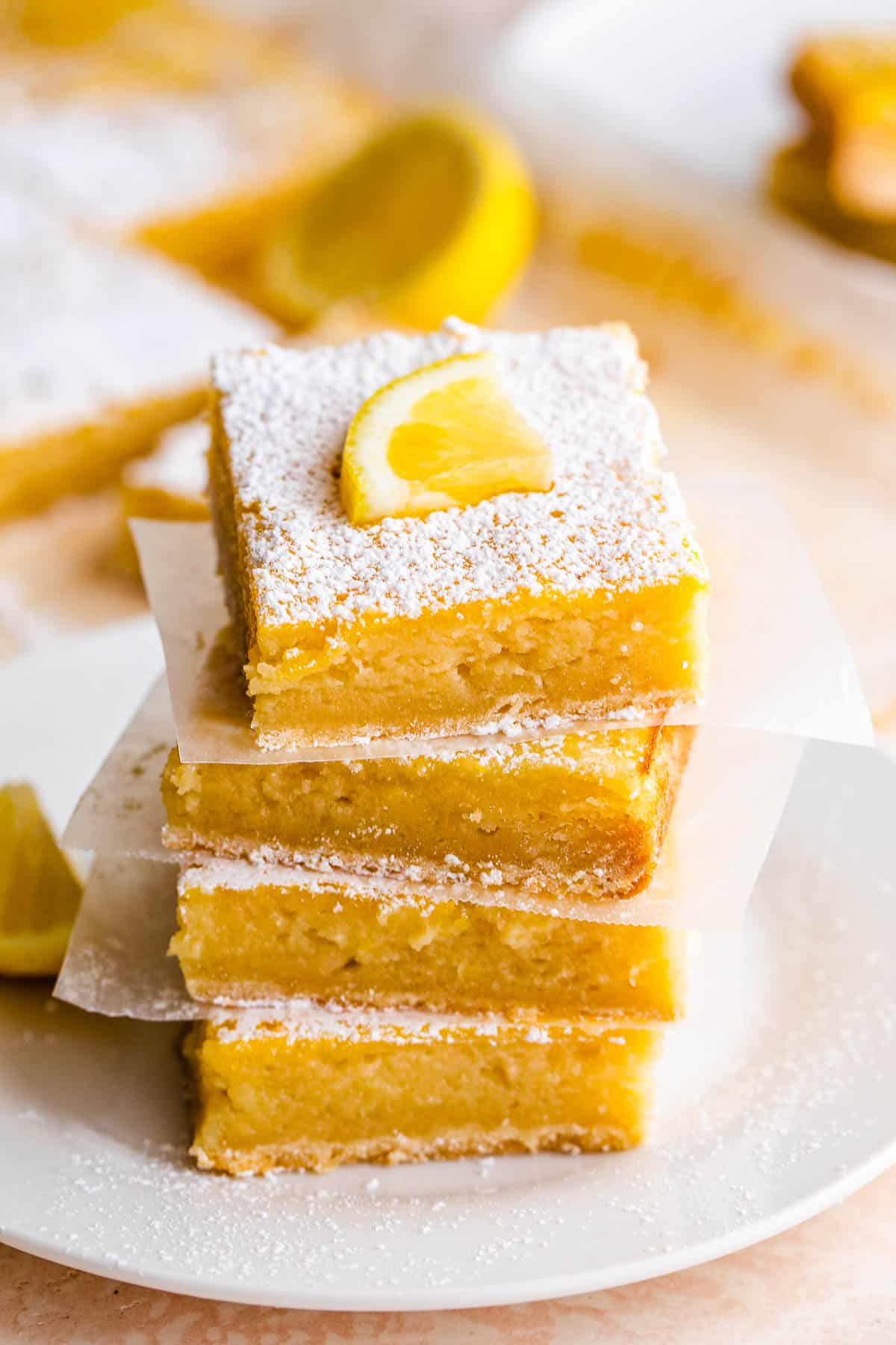 four lemon bars stacked one on top of the other and finished with a powdered sugar dusting and a lemon slice on top