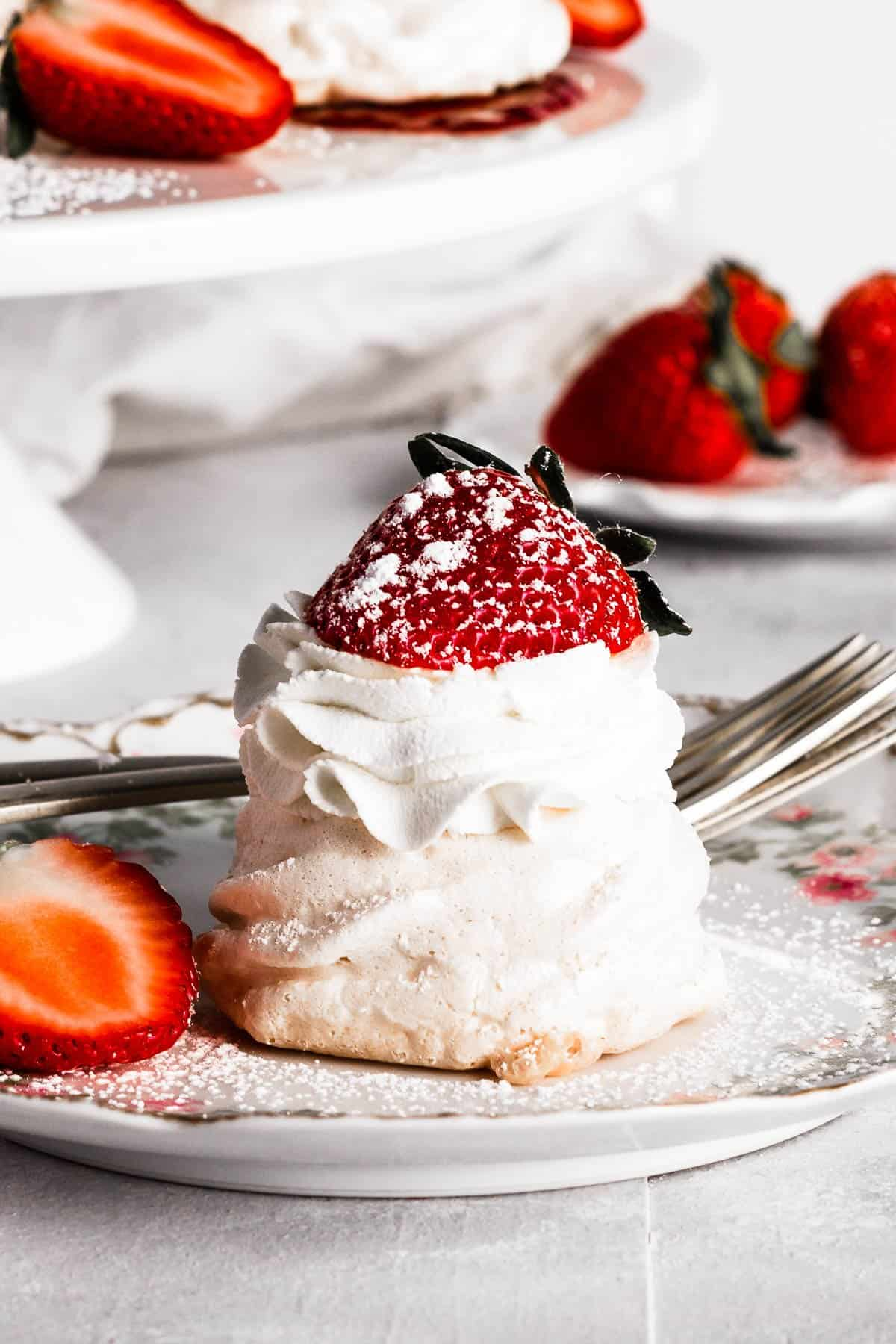 mini strawberry pavlova topped with whipped cream, strawberries, and a dust of powdered sugar