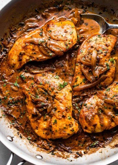 close up overhead shot of four chicken breasts cooking in a skillet with onions and gravy